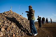 Men pour vodka onto a prayer mound overlooking downtown Ulaanbaatar while a local crew films a music video. Ancient shamanistic traditions have persisted in the modern practice of Buddhism in Mongolia.