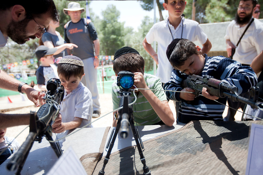 Jewish Orthodox Israeli children play with rifles during a traditional display of military weapons, part of the celebrations for Israel's Independence Day marking the 63rd anniversary of the creation of the state, at the Ammunition Hill national memorial site in Jerusalem on May 10, 2011.