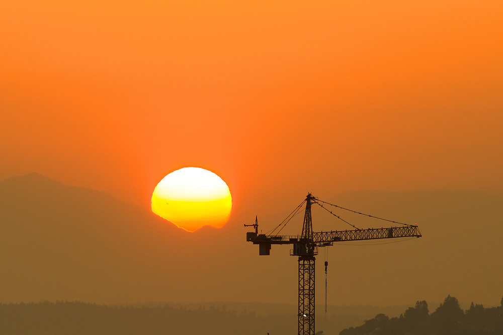 Silhouette of a construction tower against a setting sun.