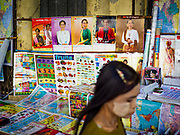 18 NOVEMBER 2017 - YANGON, MYANMAR: A Burmese woman walks past a street stand selling calendars with Aung San Suu Kyi's picture. Pope Francis is visiting Myanmar, September 27-30. It will be the first visit by a Pope to the overwhelmingly Buddhist nation. He will meet with the Aung San Suu Kyi and other political leaders and will participate in two masses in Yangon. The Pope is expected to talk about Rohingya issue while he is in Myanmar. The Rohingya are persecuted Muslim minority in Rakhine state in western Myanmar. It's not clear how Myanmar's politically powerful nationalist monks will react if the Pope openly talks about the Rohingya. In the past, the monks have led marches and demonstrations against foreign diplomatic missions when foreign ambassadors have spoken in defense of the Rohingya. Suu Kyi has been criticized in the international media for not doing enough to stop the violence against the Rohingya. There is not much visible sign of the Pope's imminent visit in Yangon, which is estimated to be more than 90% Buddhist.    PHOTO BY JACK KURTZ
