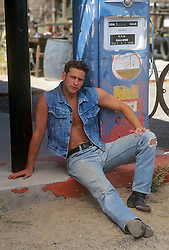 man with an open shirt at an old gas station sitting my the gas pumps