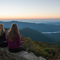 Sunrise at the top of Craggy Pinnacle Trail along the Blue Ridge Parkway northeast of Asheville, North Carolina. Two young model released women watch the sun rise.
