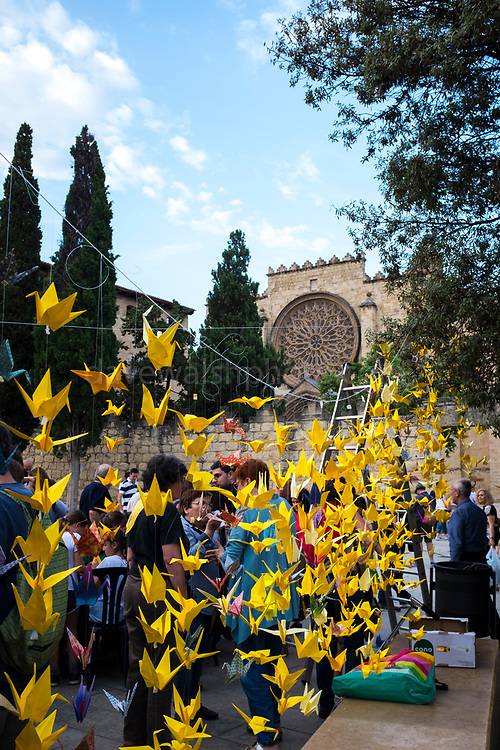 1000 Grues per les llibertats - 1000 paper cranes being made in Placa Octavia, Sant Cugat, to support demands to release former Catalan foreign minister Raul Romeva, who is currently being held without trial in a Spanish prison, in Estremera, for his part in the Oct 1 2017 Catalan independence referendum. Romeva is a resident of Sant Cugat del Valles. Japanese legend promises that those who fold a thousand origami cranes will be granted a wish - in this case, the release.<br /> <br /> Jailed without bail: 2 Nov 2017<br /> Granted bail: 4 Dec 2017<br /> Re-imprisoned: 23 Mar 2018<br /> Charges: rebellion, sedition and misuse of public funds
