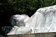 10 year old child standing beside the Tuong Phat Nam (white reclining Buddha), on Ta Cu mountain, Binh Thuan Province, Vietnam. At 49 metres long, the Buddha is the longest in Vietnam and one of the longest reclining Buddhas in Asia.