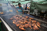 Cooking jerk chicken on Sunday 28th August 2016 at the 50th Notting Hill Carnival in West London. A celebration of West Indian / Caribbean culture and Europes largest street party, festival and parade. Revellers come in their hundreds of thousands to have fun, dance, drink and let go in the brilliant atmosphere. It is led by members of the West Indian / Caribbean community, particularly the Trinidadian and Tobagonian British population, many of whom have lived in the area since the 1950s. The carnival has attracted up to 2 million people in the past and centres around a parade of floats, dancers and sound systems.