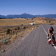A touring cyclist rides uphill away from the rockies in the dry lowlands of Central Colorado while bicycling across the USA .Photo by Roger S. Duncan.  ...