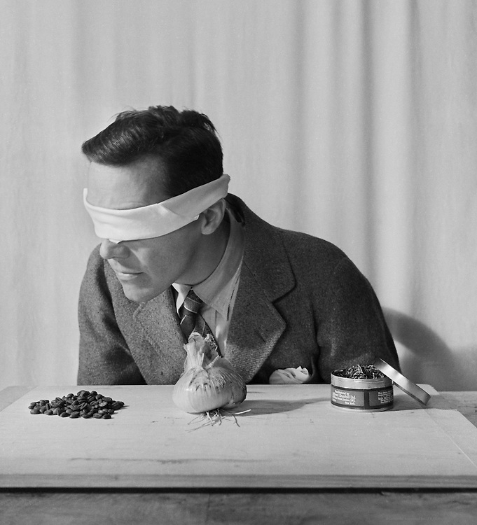 Testing the Senses: Smell. Man with Blindfold on His Eyes Identifying Different Foods, England, 1935