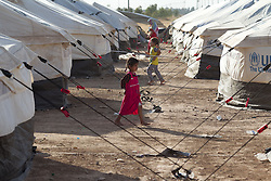 © Licensed to London News Pictures. 25/06/2014. Khanaqin, Iraq. A young Iraqi refugee walks between tents at a refugee camp on the outskirts of Bahari Taza village in Iraq. Located on the outskirts of Khanaqin, a town just 20 minutes from the front-line of the battle with ISIS insurgents, the Bahari Taza refugee camp, and its satellite camps, now house around 600 families from southern Iraq. Built by the local village leader to meet the influx of refugees from nearby Jalawla and Saidia, where intense fighting is still taking place. Turkman, Arab and Kurd, both Sunni and Shia, all live together in tents, barns and unfinished buildings waiting for the conflict to end. Photo credit: Matt Cetti-Roberts/LNP