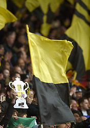 Watford fans in the stands hold a trophy in support of their team