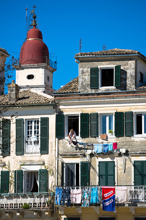 Greek woman hanging out washing on line from window of traditional apartment in Kerkyra, Corfu Town, Greece
