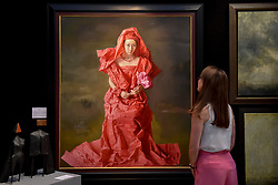 "© Licensed to London News Pictures. 27/06/2017. London, UK.  A woman views ""Red Paper Bride"" by Zeng Chauanxing at The Arts & Antiques Fair taking place at Olympia in Kensington.  The event is the UK's largest and most established art and antiques fair and runs until 2 July. Photo credit : Stephen Chung/LNP"