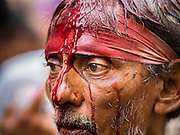 04 NOVEMBER 2014 - YANGON, MYANMAR:  Blood streams down the face of a Burmese Shia man who participated in the flagellation for Ashura in Yangon. Ashura, commemorates the death of Hussein ibn Ali, the grandson of the Prophet Muhammed, in the 7th century. Hussein ibn Ali is considered by Shia Muslims to be the third imam and the rightful successor of Muhammed. He was killed at the Battle of Karbala in 610 CE on the 10th day of Muharram, the first month of the Islamic calendar. According to Myanmar government statistics, only about 4% of the population is Muslim. Many Muslims have fled Myanmar in recent years because of violence directed against Burmese Muslims by Buddhist nationalists.    PHOTO BY JACK KURTZ