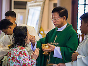 15 FEBRUARY 2015 - BANGKOK, THAILAND: The priest serves communion during mass at Santa Cruz Catholic Church in the Kudeejeen neighborhood in Bangkok. Santa Cruz church was established in 1770  and is one of the oldest and most historic Catholic churches in Thailand. The church was originally built by Portuguese soldiers allied with King Taksin the Great. Taksin authorized the church as a thanks to the Portuguese who assisted the Siamese during the war with Burma. Most of the Catholics in the neighborhood trace their family roots to the original Portuguese soldiers who married Siamese (Thai) women. There are about 300,000 Catholics in Thailand in about 430 Catholic parishes and about 660 Catholic priests in Thailand. Thais are tolerant of other religions and although Thailand is officially Buddhist, Catholics are allowed to freely practice and people who convert to Catholicism are not discriminated against.      PHOTO BY JACK KURTZ