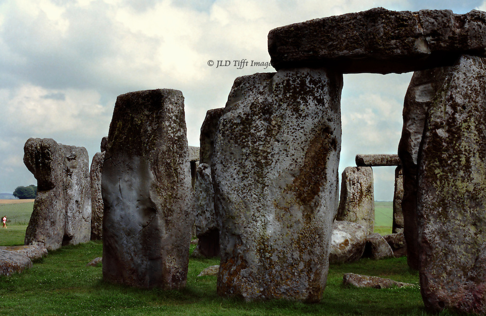 Stonehenge, closeup of a group of the central bluestone structures.  In the distance, a hiker is seen.