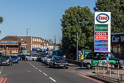 Licensed to London News Pictures. 24/09/2021. London, UK. Large queues at an Esso petrol station near the A3 in New Malden south-west London this afternoon as oil giants struggle to maintain deliveries due to the lack of HGV drivers as the fuel shortage crisis continues. Photo credit: Alex Lentati/LNP
