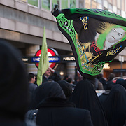LONDON, ENGLAND - DECEMBER 27:  Shia Muslim women with a  Imam Hussein flag at the  Ashura procession in Central London on December 27, 2009 in London, England. Ashura is a 10 day period of mourning for Imam Hussein, the seven-century grandson of Prophet Mohammad who was killed in a battle in Karbala in Iraq, in 680 AD.  (Photo by Marco Secchi/Getty Images)