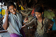 Arti, 19,  (left) is talking to relatives on the family's mobile phone while her youngest sister Poonam, 13, is standing next to her, in the court yard of their newly built home in Oriya Basti, one of the water-contaminated colonies in Bhopal, central India, near the abandoned Union Carbide (now DOW Chemical) industrial complex, site of the infamous '1984 Gas Disaster'.