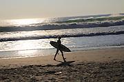 Surfer with board walking on El Palmar beach, Vejer de la Frontera, Cadiz Province, Spain