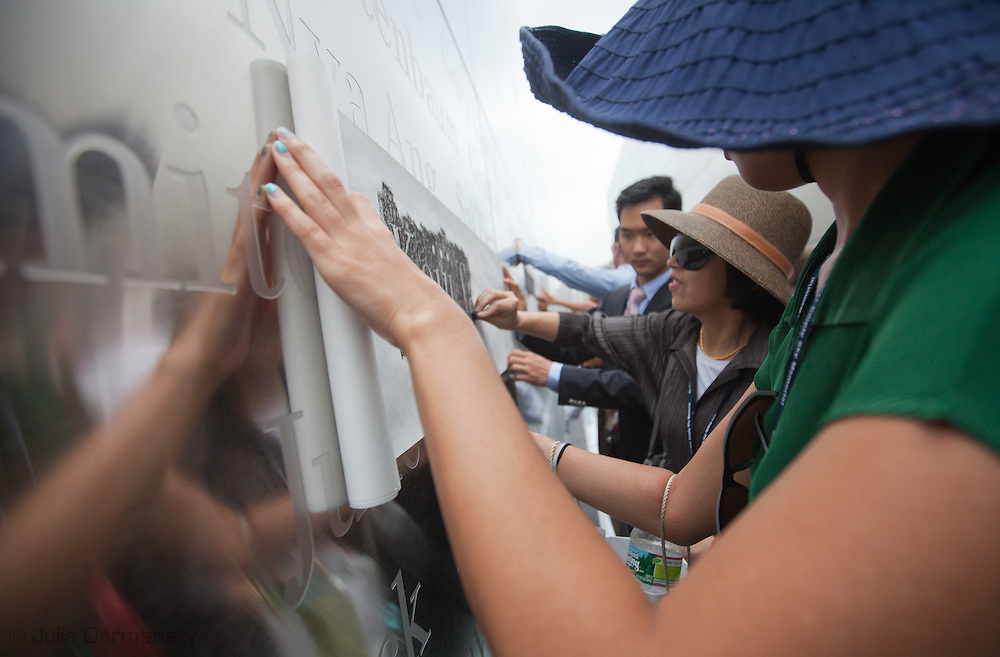 Family members make a rubbing off one of the names etched in stainless steel of the 746 New Jerseyans who perished after the terrorist attacks on 9/11, 2001 during the opening of the Empty Sky Memorial 9/11 Memorial at Liberty State Park in New Jersey on  September 10th 2011 for the tenth anniversary of 9/11.The memorial is two 30-Ft rectangular towers  208 feet by 10 inches long,  the width of the World Trade Center towers and with the names of the 746 New Jerseyans who perished after the terrorist attacks on 9/11, 2001.