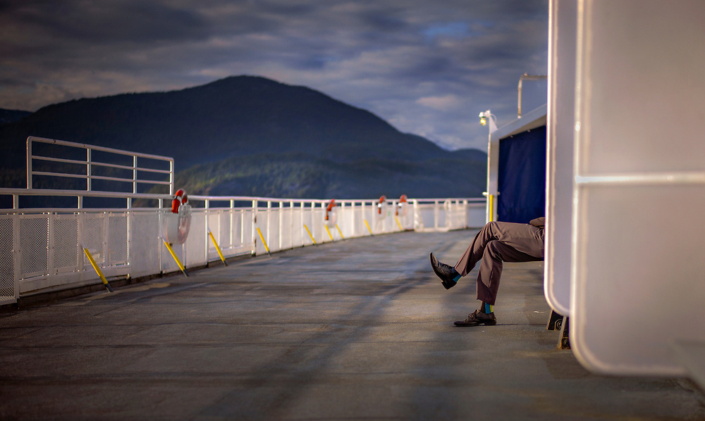 A passenger on board the BCFerries Queen of Surrey sits on the outside deck while sailing to Langdale from Horseshoe Bay in West Vancouver, British Columbia.  (2018)