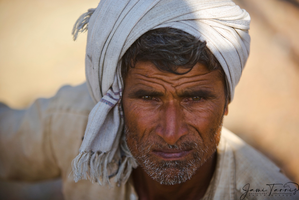 Close up portrait of a man with a white turban and a serious expression,Pushkar camel fair, Rajasthan, India