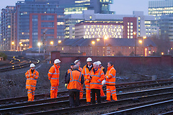 © Licensed to London News Pictures . 23/01/2013 . Manchester , UK . National Rail staff on the closed line . A derailed train on a busy stretch of track between Manchester and Salford today (23rd January 2013) . The accident has closed many major commuter routes adjacent to the track including the city's A57M Regent Road . Photo credit : Joel Goodman/LNP