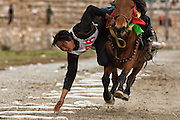Grabbing scarves event at the Horse Racing Festival or 'Heavenly Steed Festival' which takes place on the 5th and 6th days of the fifth lunar month. They run around the track once and on both straight sections there are scarves laid out on the ground.  The winner is the rider who collects the most scarves in the shortest time. Zhongdian. Deqin Tibetan Autonymous Prefecture. Yunnan Province. CHINA<br /> Horse traders come from distant villages to compete and trade. The horses are decorated with fine Tibetan carpet saddle blankets and silk scarves tied on their tails, manes and bridles.  Families camp out in their traditional tents in the horse racing grounds. Large picnics are laid out and there is a lively sense of celebration as competing riders test their equestrian skills and try to win honour for their home villages. There are over 100,000 Tibetans in China and they are mostly concentrated in Deqin with smaller communities in Lijiang, Yongsheng, Gongshan and Ninglang.