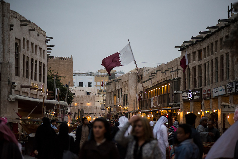 People walk on a windy winter evening at Souk Waqif in Doha, Qatar.