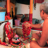 Asia, India, Calcutta. Shrine by the River Hooghly in Calcutta, where a Bengali man offers water.