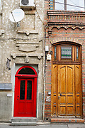 red door in a dilapidated building deterioration, Bucharest Romania