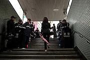 Frau mit einem rosa Regenschirm am Tag der Feierlichkeiten von Buddhas Geburtstag (2. Mai 2009) an einem von koreanischen Polizisten bewachten Ausgang der Metro in Seoul im Zentrum der koreanischen Metropole.<br /> <br /> Woman with a pink umbrella leaving an exit of the Seoul metro protected by police man on the day of Buddhas birthday (2nd of May 2009) in the center of the Korean metropolis Seoul.