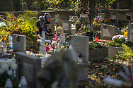 A woman takes a picture with her mobile phone of a grave in Rakowicki cemetery in Krakow, Poland 2019.