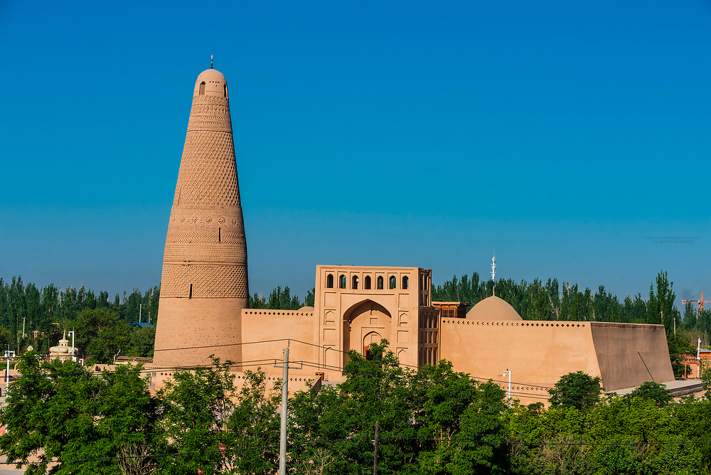 Uyghur mosque and Emin minaret, Turpan, Xinjiang Province, China. The minaret was built in 1777 is a 141 foot conical tower. Turpan is a small oasis town and former Silk Road outpost located in a depression 80m below sea level.