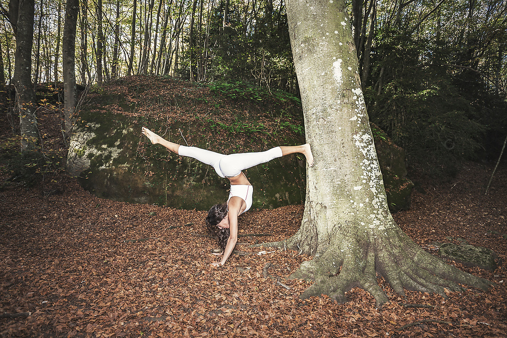 Woman doing yoga headstand with split legs in forest