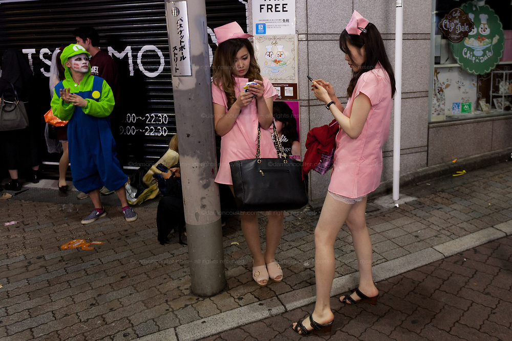 Two young Japanese women dressed as sexy nurses during the Halloween celebrations Shibuya, Tokyo, Japan. Sunday morning October 28th 2018