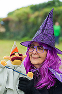Merrick, New York, USA. October 29, 2016. BETTY TUCKER, of Merrick, dressed as a witch and holding a wizard puppet, is at the 2016 annual Merrick Spooktacular hosted in part by the North and Central Merrick Civic Association (NCMCA). Betty is a member of the Merrick American Legion Auxilliary 1282, and the post sponsored the holiday party at Fraser Park.