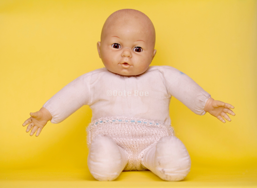 a baby doll with arm stretched against a yellow background
