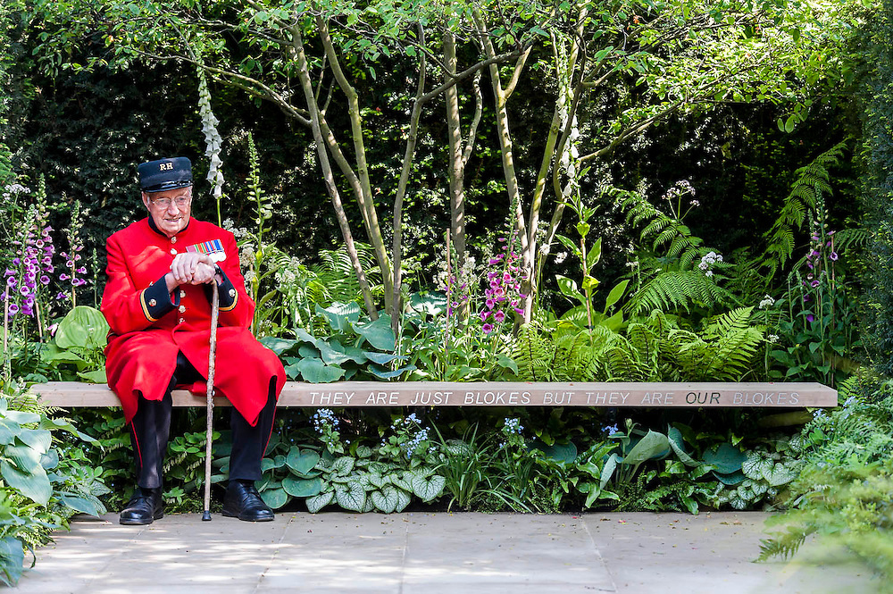 A Chelsea pensioner enjoys the shade.  The 'Hope on the Horizon' garden in aid of Help for Heroes: produced by building and landscaping firm Farr and Roberts', making their debut; designed by Matthew Keightley (29), as a result of his brother Michael's involvement with the armed forces, having served on four tours to Afghanistan and due for his fifth this year; and sponsored by the David Brownlow charitable foundation. The garden layout is based on the shape of the Military Cross, the medal awarded for extreme bravery. Granite blocks will represent the soldiers' physical wellbeing and the planting represents their psychological wellbeing at various stages of their rehabilitation. Both evolve through the garden from a rough, unfinished, over-grown beginning through to a perfectly sawn, structured end. An avenue of hornbeams draws the attention through the entire garden to a sculpture resembling a hopeful horizon; a reminder to the soldiers that they all have a bright future ahead. As well as areas to recline and reflect, the garden offers focal points all the way through. Cool, calming colours are used throughout, helping to emphasise the fact that it will be a serene, contemplative space. After the Show, the garden will be moved and set within the grounds at Help for Heroes Recovery Centre at Chavasse VC House in Colchester, Essex. The garden will offer a serene, peaceful haven to contemplate and inspire a bright future and to support the challenging journey to recovery. The Chelsea Flower Show 2014. The Royal Hospital, Chelsea, London, UK