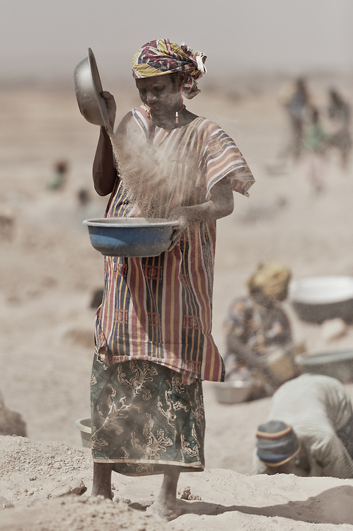 Stock photograph of African women in Burkina Faso dry panning or air panning for gold from old muck piles.