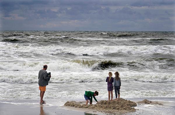 Nederland, the netherlands, Wijk aan zee,1-9-2018 Aan zee . Door de stevige wind worden de golven hoger en woester. Kinderen spelen op het strand aan de waterlijn.Foto: Flip Franssen