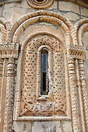 Pictures & images of Nikortsminda ( Nicortsminda ) St Nicholas Georgian Orthodox Cathedral exterior and its Georgian relief sculpture stonework window decorations, 11th century, Nikortsminda, Racha region of Georgia (country). A UNESCO World Heritage Tentative Site. .<br /> <br /> Visit our MEDIEVAL PHOTO COLLECTIONS for more   photos  to download or buy as prints https://funkystock.photoshelter.com/gallery-collection/Medieval-Middle-Ages-Historic-Places-Arcaeological-Sites-Pictures-Images-of/C0000B5ZA54_WD0s<br /> <br /> Visit our REPUBLIC of GEORGIA HISTORIC PLACES PHOTO COLLECTIONS for more photos to browse, download or buy as wall art prints https://funkystock.photoshelter.com/gallery-collection/Pictures-Images-of-Georgia-Country-Historic-Landmark-Places-Museum-Antiquities/C0000c1oD9eVkh9c