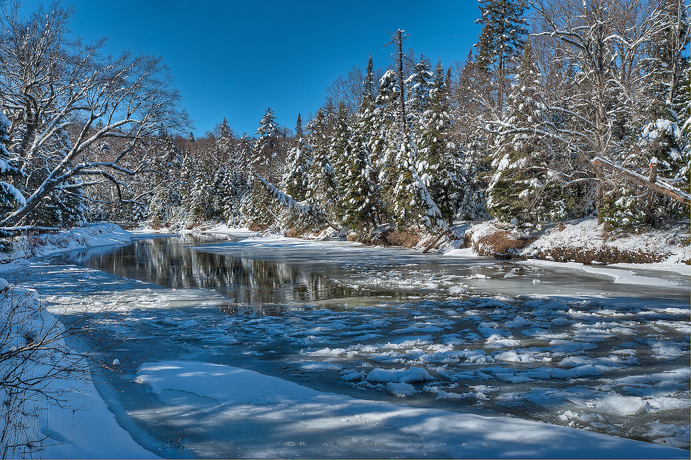 """Ausable River, Adirondacks, NY. Below the Lake Placid ski jumps, the Ausable becomes more of a meadow stream, slowing to a meander through meadows and boreal forest. Walking the woods parallel to the river proved challenging in trying to find shooting vantage points...the ice near the banks was untrustworthy as the day was coming to an end, and often there was too much foliage in the way--even in winter-- for an unobstructed view. The stretch of water disappearing into the ice attests to recent temperatures, an unusually mild winter in New York's Adirondacks. Sometimes the range of shadow exposure to brightness exposure overwhelms the camera. Such was the case with this scene, that if I exposed for the snow the shadows went black, and for the shadows, the snow became a meaningless white glare. Thus I took 5 exposures, and used three, blending the exposures in a software program called Photomatix. Through a series of sliders one can even out the shadows and brightness...hopefully. That is, it doesn't always come out as you want. So it is a tool, sometimes not the right tool. Adjustments range from realistic to a look like a painting; I adjust to where I like it...this is artist discretion. I tend to lean towards realism, but what is the artist doing if not making you feel his own impression? If you feel this is """"cheating"""", consider that even with film and darkroom print making, the greats """"burned and dodged"""" the prints during the film to paper process to brighten those shadows or darken those highlights. Photography to art is always manipulation."""