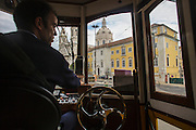 The driver of a traditional Lisbon tram driving liner 28 in front of Estrela Basilica church.