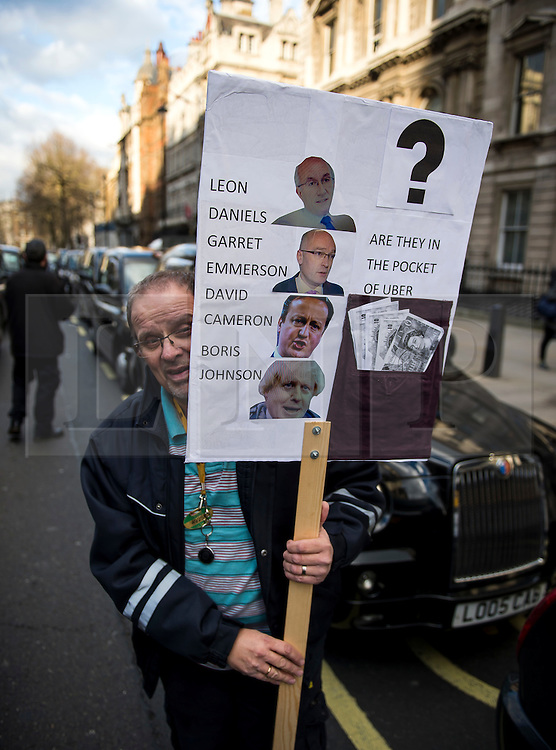 © Licensed to London News Pictures. 10/02/2016. London, UK. A black cab driver holding a placard as London black cab drivers stage a protest in Westminster, London against Government interference in the taxi industry and 'active support' for Uber, which they allege is a 'tax avoiding global corporation' Photo credit: Ben Cawthra/LNP