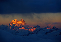 Russia, Caucasus, Mount Ushba (4710 m asl), just on the Georgian side of the border, is lit by red light just before sunset. The valley below is covered by clouds and fog.<br /> Seen from Elbrus.