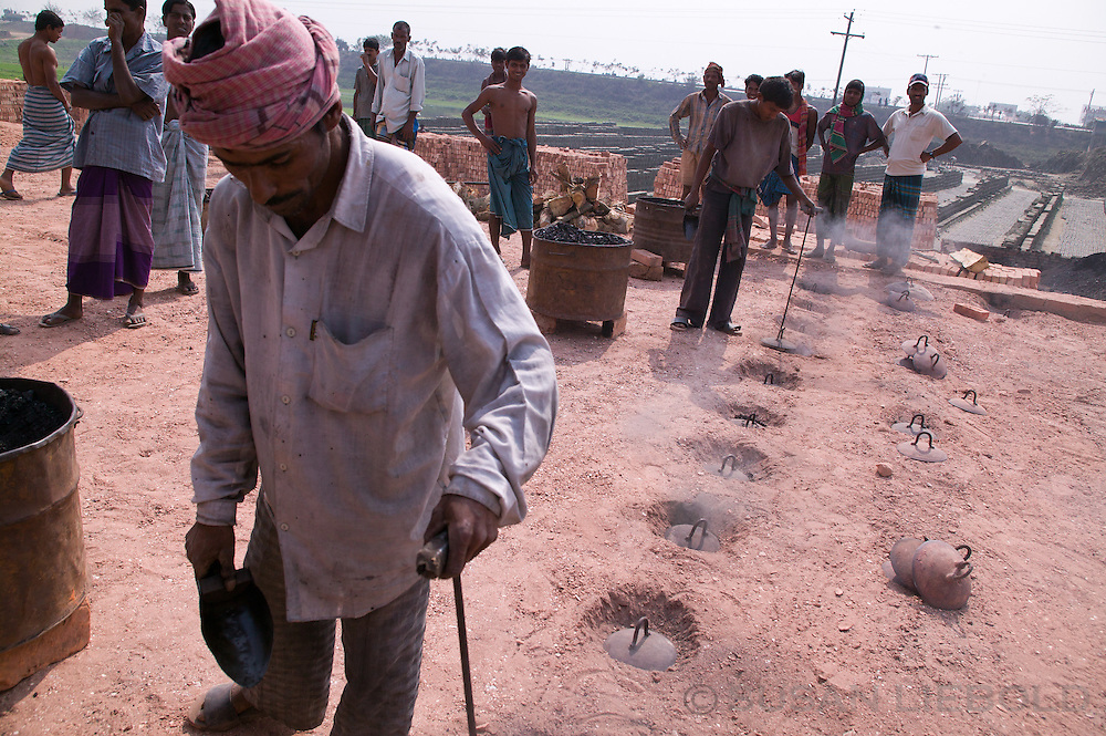 Man pouring coal into the brick burning kiln through small holes in the ground in Bangladesh.