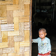 A young Lao girl stands in the doorway of her bamboo house in a village near Vieng Xai in Houaphanh Province in northeastern Laos.
