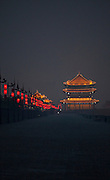 A traditional Chinese gate is illuminated a night a top the Xian City walls