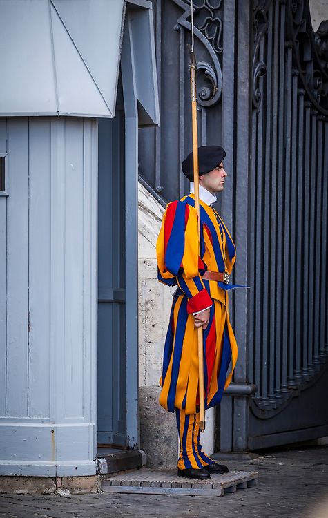 A Pontifical Swiss Guard stands outside an entrance to St. Peters Basilica, Vatican City, Rome, Italy.