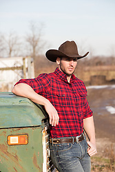 rugged cowboy leaning against an old truck outdoors